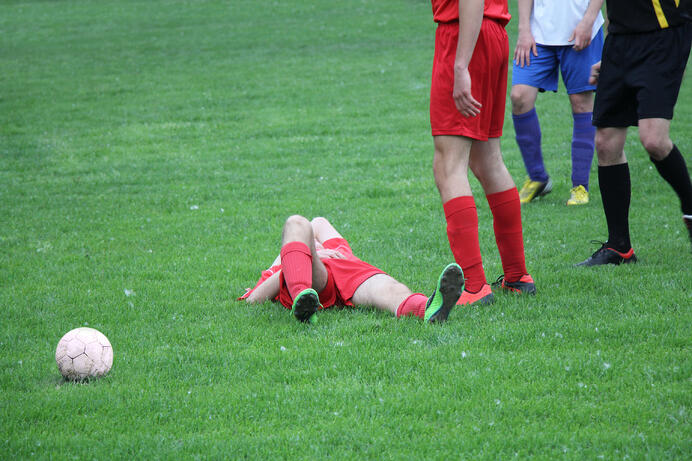 graphicstock-injured-player-at-the-football-match-lying-on-the-grass_SOIL5mVd-