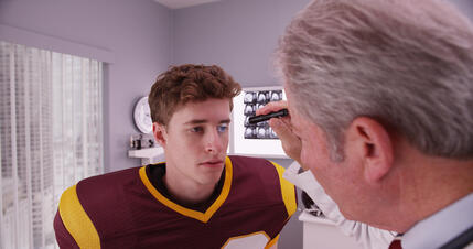 storyblocks-mid-aged-doctor-examining-football-player-after-concussion_B04bXlpja_m